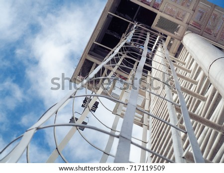 Fixed ladder to top of building or observation deck with background is blue sky.