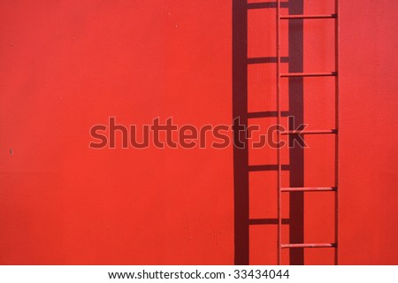 Fixed red ladder with copy space. Detail from a ship. Ladder in focus. - stock photo