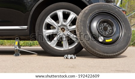 Fixing a puncture at the roadside with a view of the car jacked up with the spare tyre balanced against the side and nuts removed off the wheel - stock photo