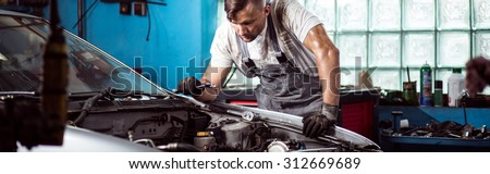 Fixing car engine in automobile repair shop - stock photo