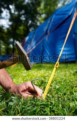 Fixing of blue tent in camp - stock photo
