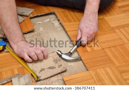 Fixing with tools wooden parquet in the apartment damaged by moisture or water