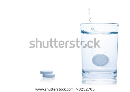 Fizzy pill splash in a glass of water, isolated on the white background, clipping path included. - stock photo