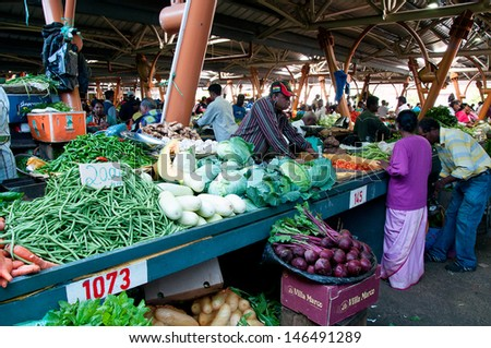 FLACQ, MAURITIUS-JUNE 23: Indian people and tourists search for a bargains in the market hall on June 23, 2013 in Flacq, Mauritius - stock photo
