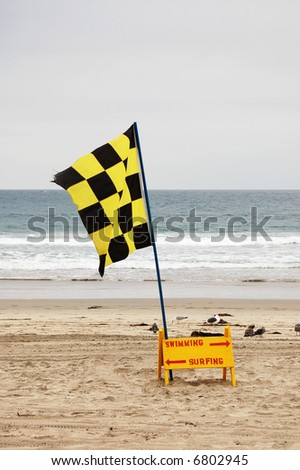 Flag and sign showing swimming and surfing areas on the beach; Mission Beach; San Diego, California - stock photo