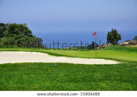Flag blows in the wind on a green with ocean in background. - stock photo