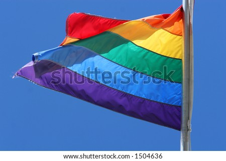 flag in the colors of the rainbow flying against a clear blue sky - stock photo