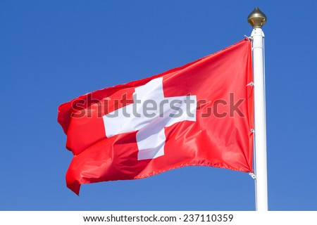 Flag of a Switzerland on a background blue sky - stock photo