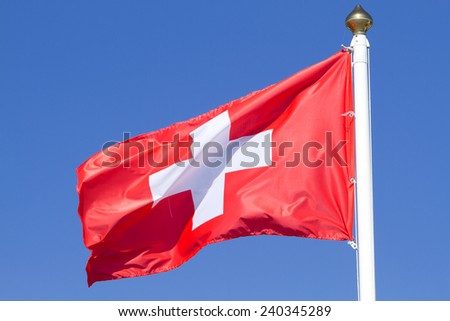 Flag of a Switzerland on a  blue sky  - stock photo