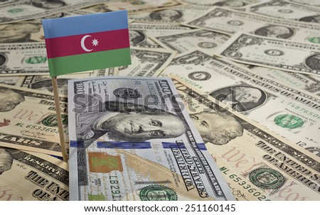 Flag of Azerbaijan sticking in a variety of american banknotes.(series) - stock photo