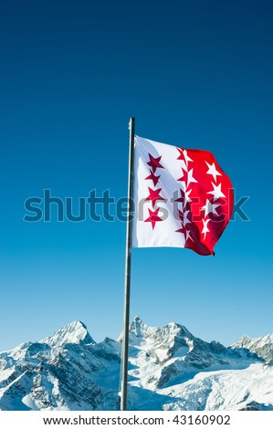 Flag of canton Wallis, Switzerland with snow mountains in the background, Zermatt, Switzerland - stock photo