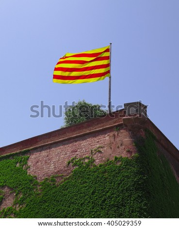 Flag of Catalonia fluttering in the wind against clear blue sky. Montjuic castle in Barcelona, Spain - stock photo
