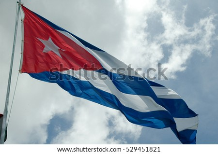 Flag of Cuba hoisting proudly in the air on a bright day with blue sky and clouds.