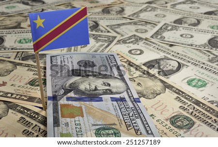 Flag of Democratic Republic of the Congo sticking in a variety of american banknotes.(series) - stock photo