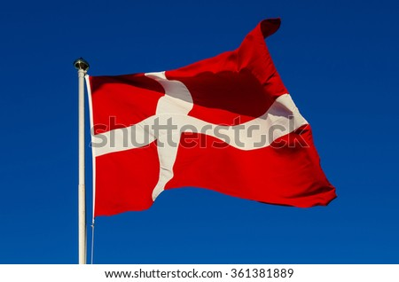 Flag of Denmark against the blue sky, national patriotic background - stock photo