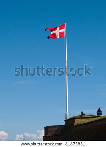 Flag of Denmark up high in the air with blue sky background - stock photo
