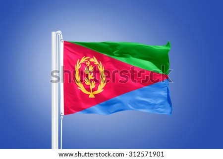Flag of Eritrea flying against a blue sky. - stock photo