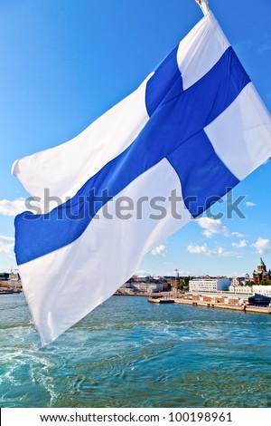 Flag of Finland against Helsinki cityscape - stock photo