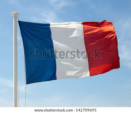 Flag of France waving against blue sky - stock photo