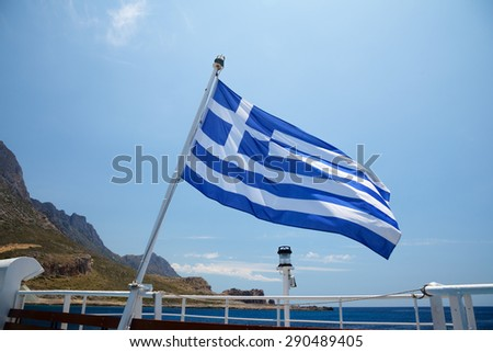 Flag of Greece on a cruise ship against greek coastline - stock photo