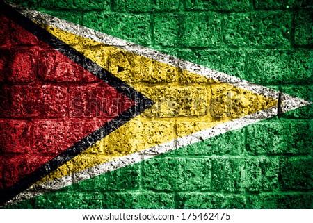 Flag of Guyana painted onto a grunge brick wall  - stock photo