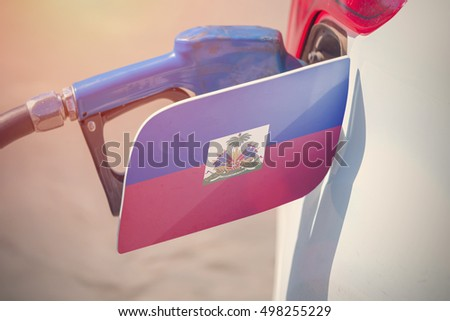 Flag of Haiti on the car's fuel filler flap with gas pump nozzle in the tank