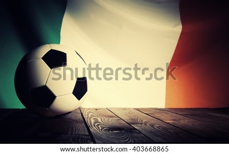 Flag of Ireland with football on wooden boards as the background. Vintage Style. - stock photo