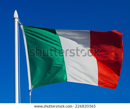 Flag of Italy in flight against blue sky during wind