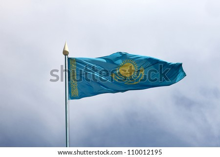 Flag of Kazakhstan is waving on the sky background - stock photo
