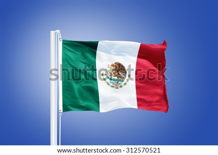 Flag of Mexico flying against a blue sky. - stock photo