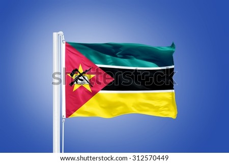 Flag of Mozambique flying against a blue sky. - stock photo