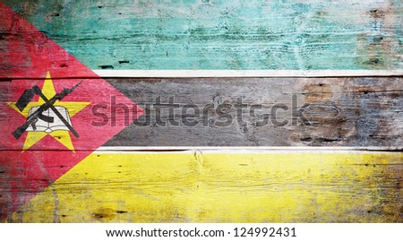 Flag of Mozambique painted on grungy wood plank background - stock photo