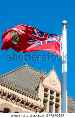 Flag of Ontario and old city hall in Toronto in a blue sky day - stock photo