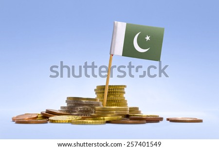Flag of Pakistan in a mixed stack of european coins and a blue background.(series) - stock photo
