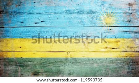Flag of Rwanda painted on grungy wood plank background - stock photo