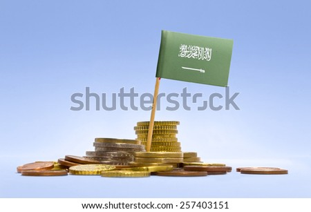 Flag of Saudi Arabia in a mixed stack of european coins and a blue background.(series) - stock photo