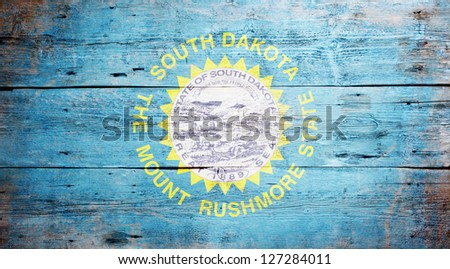 Flag of South Dakota painted on grungy wooden background - stock photo