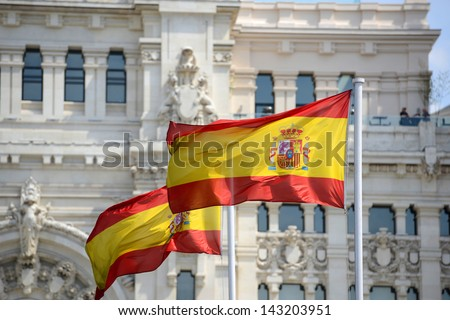 Flag of Spain in the wind in front of Palace of Communication (Spanish: Palacio de Comunicaciones) in Madrid, Spain - stock photo