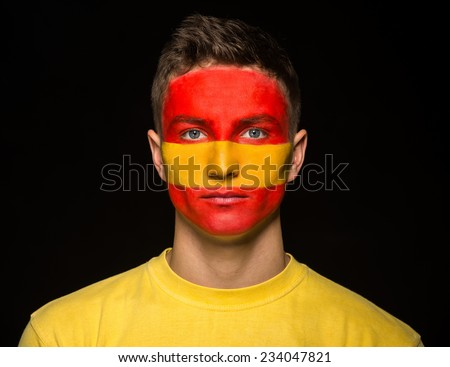 Flag of Spain painted on a face of a young man. - stock photo