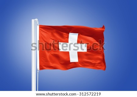 Flag of Switzerland flying against a blue sky. - stock photo