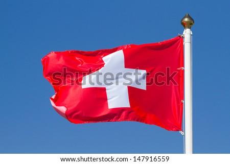 Flag of Switzerland on a background sky - stock photo