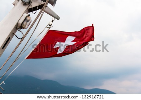 Flag of Switzerland on a ship's mast in stormy weather - stock photo