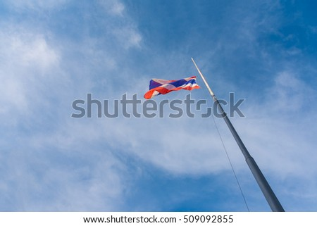 Flag of Thailand with blue sky for background.