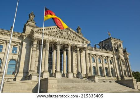 flag of the Federal Republic of Germany and entrance of the national german parliament, Berlin,  Flagge der Bundesrepublik Deutschland vor dem Eingang des Reichstages, Sitz des deutschen Bundestages - stock photo