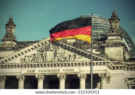 flag of the Federal Republic of Germany is waving in front of the national german parliament, vintage style, Flagge der Bundesrepublik Deutschland vor dem Reichstag, Sitz des deutschen Bundestages - stock photo