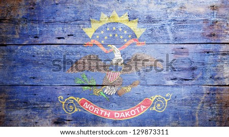 Flag of the state of North Dakota painted on grungy wooden background - stock photo