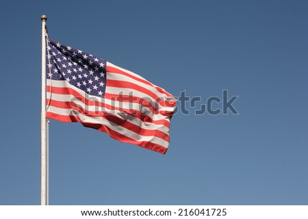 Flag of the United States of America and blue sky. - stock photo
