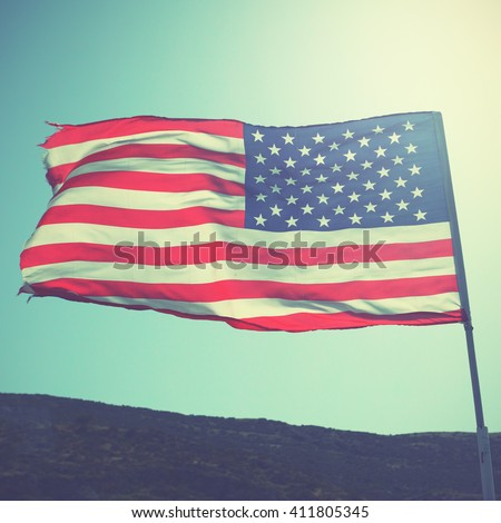 Flag of the United States of America on the wind. Retro style filtered image - stock photo