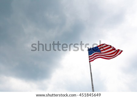 Flag of the United States of America over cloudy moody skies