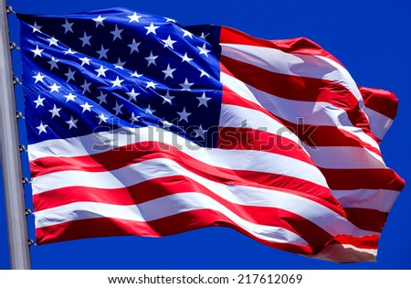 Flag of the USA against a blue sky  - stock photo